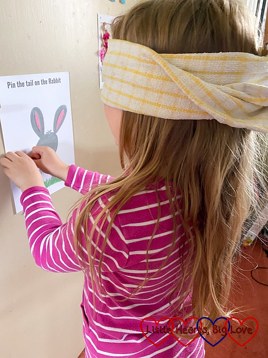 Sophie playing pin the tail on the rabbit