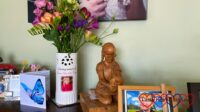 A card with a blue butterfly; a vase with Jessica's photo on full of pink and purple flowers, a wooden carving of Jessica and a photo of her on my piano