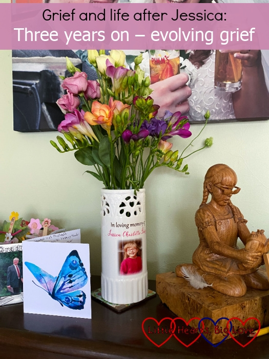 """A card with a blue butterfly; a vase with Jessica's photo on full of pink and purple flowers, a wooden carving of Jessica and a photo of her on my piano - """"Grief and life without Jessica: Three years on - evolving grief"""""""