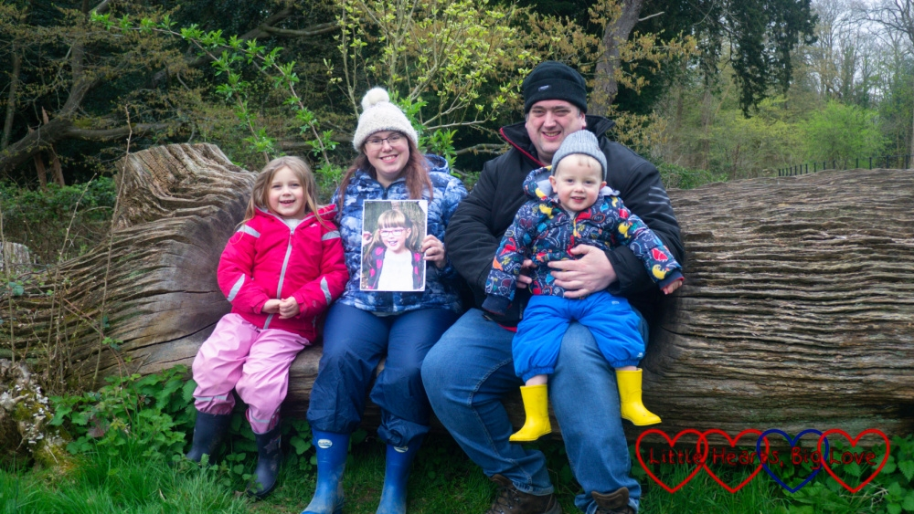 Sophie, me (holding a photo of Jessica) and hubby holding Thomas sitting on a log