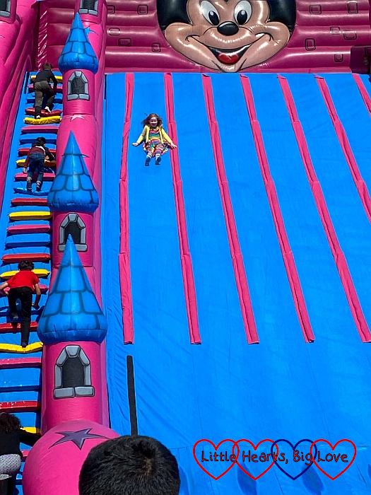 Sophie sliding down the giant inflatable slide