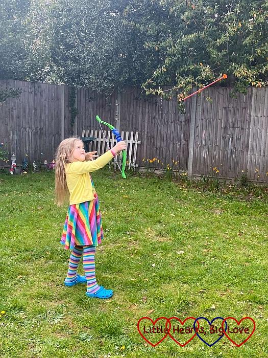 Sophie firing an arrow into the air in the garden