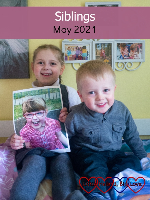 """Sophie and Thomas sitting together with Sophie holding a picture of Jessica - """"Siblings - May 2021"""""""