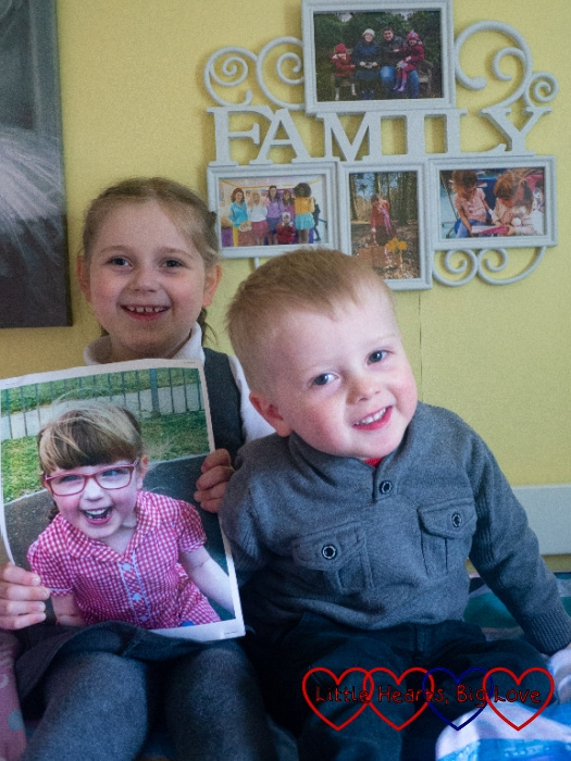 Sophie and Thomas sitting together with Sophie holding a picture of Jessica