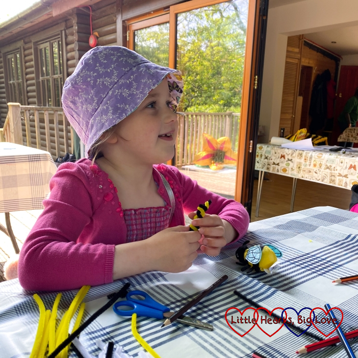 Sophie twirling yellow and black pipe cleaners around a pencil to make a bee