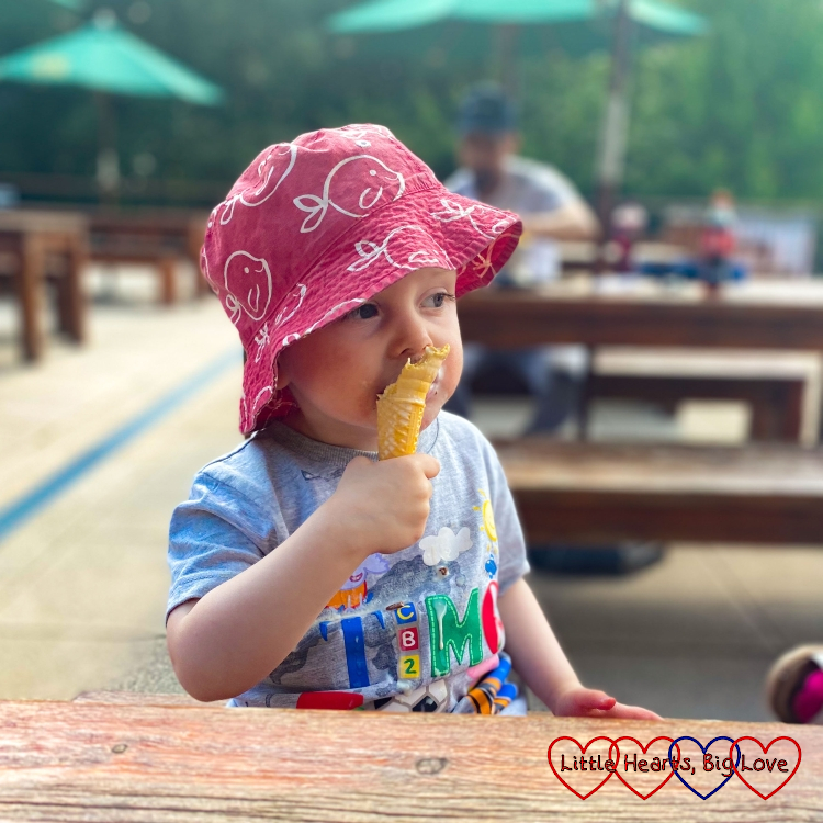 Thomas sitting at a table eating an ice-cream