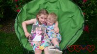 Sophie and Thomas sitting together in a green moon chair with Sophie holding a picture of Jessica
