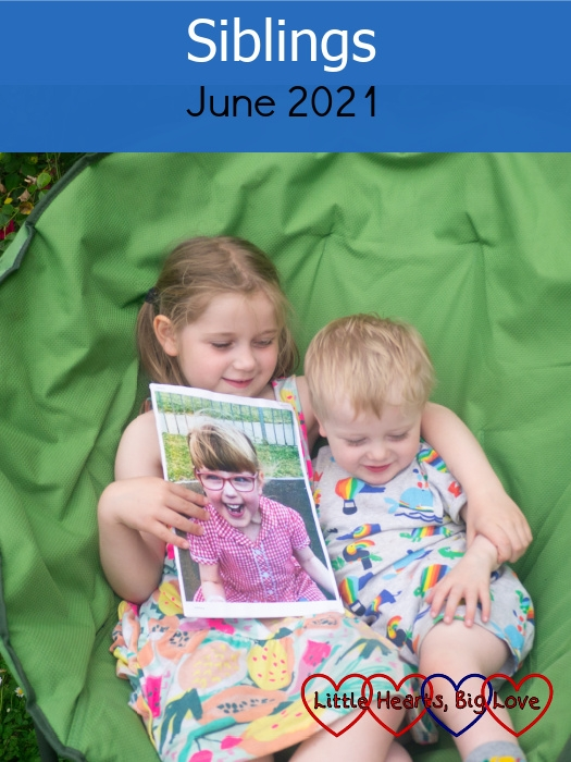 """Sophie and Thomas sitting together in a green moon chair with Sophie holding a picture of Jessica - """"Siblings - June 2021"""""""