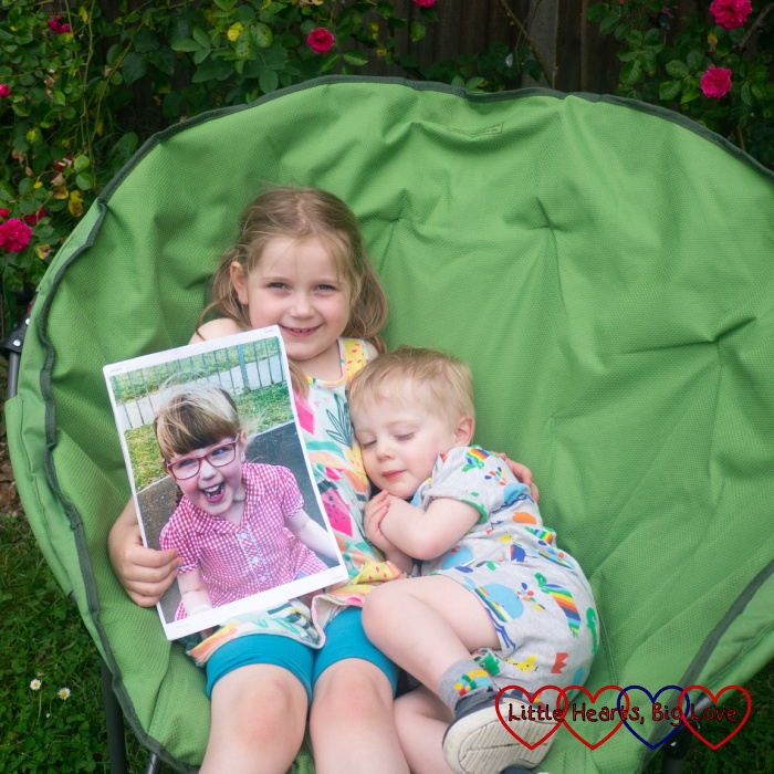 Thomas snuggling up to Sophie while sitting together in a green moon chair with Sophie holding a picture of Jessica