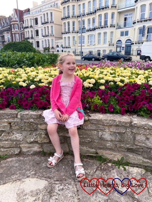 Sophie sitting on a wall with flowers behind her