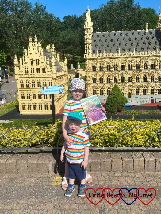 Sophie and Thomas in Miniland with Sophie holding a photo of Jessica
