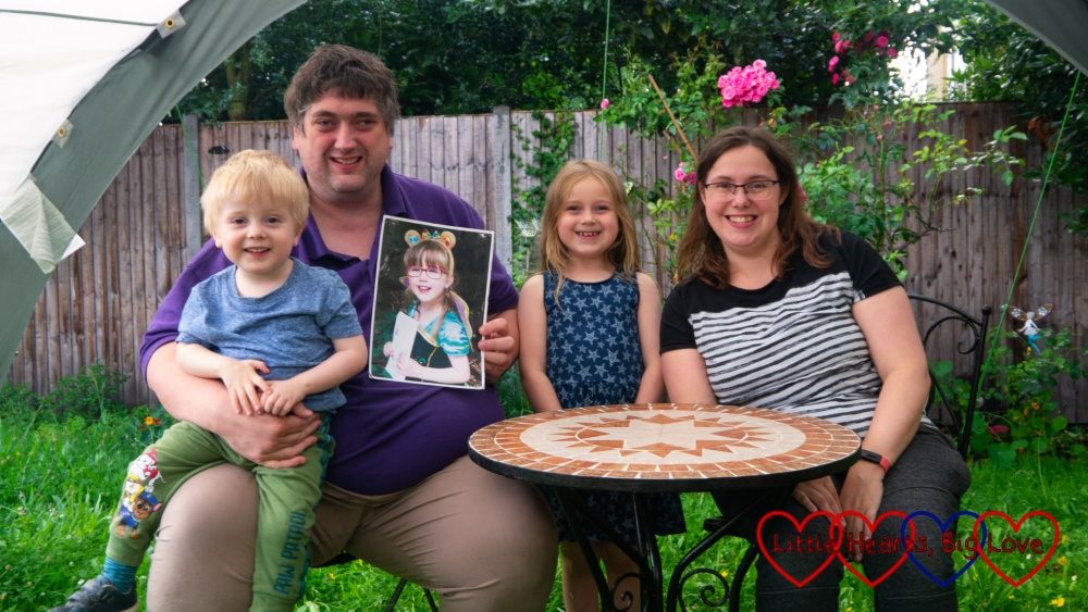 Hubby (holding a photo of Jessica) with Thomas sitting on his lap, Sophie and me out in the garden