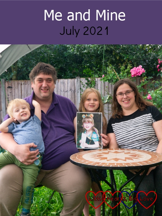"""Hubby with Thomas sitting on his lap, Sophie (holding a photo of Jessica) and me out in the garden - """"Me and Mine - July 2021"""""""