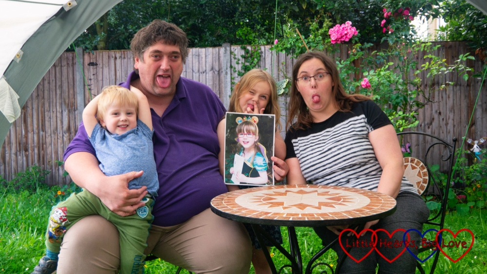 Hubby with Thomas sitting on his lap, Sophie (holding a photo of Jessica) and me out in the garden pulling funny faces