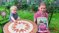 Sophie and Thomas sitting at the table in the garden with Sophie holding a photo of Jessica