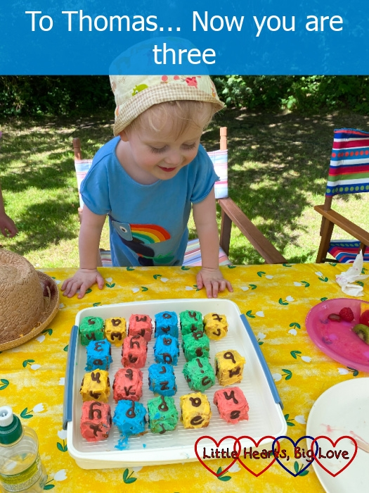 Thomas looking at his 'alphabet blocks' birthday cake which spells out 'Happy Birthday Thomas'