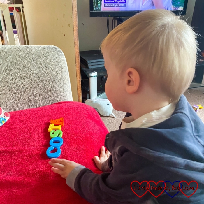 Thomas spelling out 'Costa' with his magnetic letters