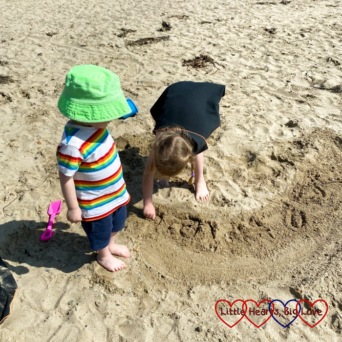 Thomas watching as Sophie writes in the sand at Baby Bay beach