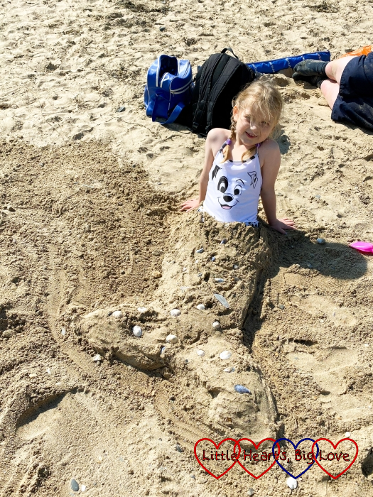 Sophie sitting on the beach with sand shaped like a mermaid's tail decorated with shells covering her legs