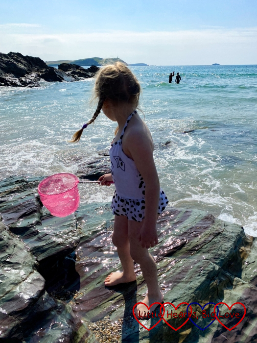 Sophie standing on the rocks at Baby Bay holding a net and looking out to sea
