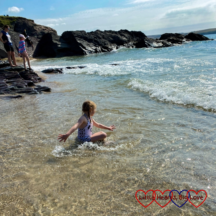 Sophie sitting in shallow water on the beach and splashing as the waves lap around her