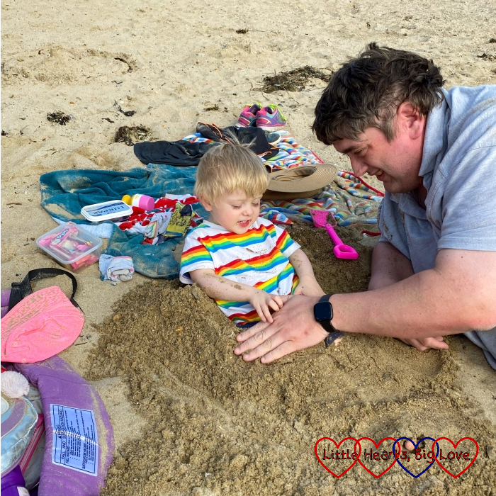 Thomas on the beach with his legs being buried in the sand by Daddy