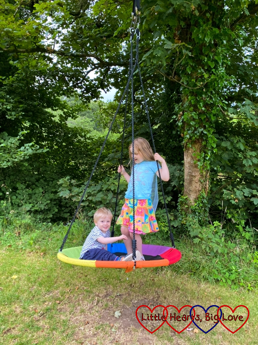 Sophie and Thomas on the large round tree swing at Coombe Mill