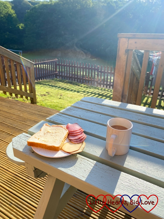 A continental breakfast and cup of tea on a picnic table out on the decking of one of the lodges at Coombe Mill looking out on the river
