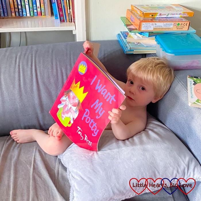 Thomas lounging on the sofa reading 'I Want My Potty'