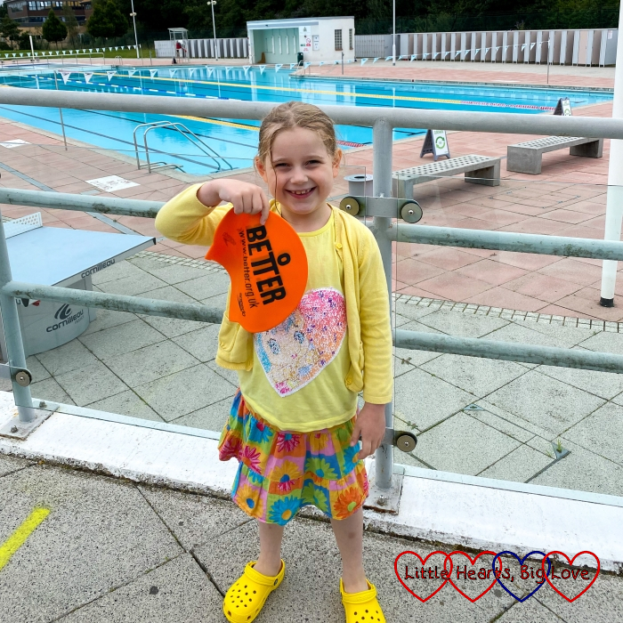 Sophie holding her amber swimming cap outside the outdoor pool