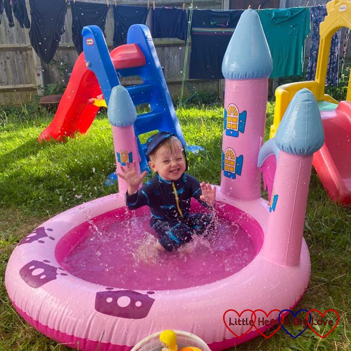 Thomas splashing in a small pink castle paddling pool