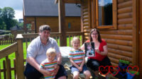 Hubby, Thomas and Sophie (in matching rainbow striped tops) and me (holding a photo of Jessica) outside our lodge at Coombe Mill