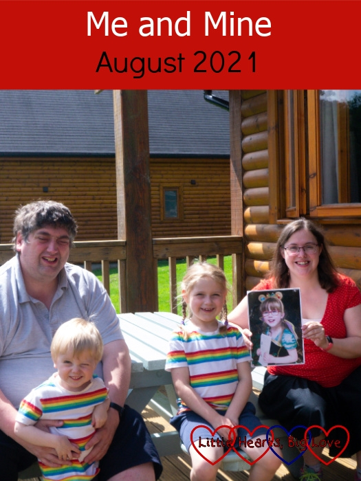 """Hubby, Thomas and Sophie (in matching rainbow striped tops) and me (holding a photo of Jessica) outside our lodge at Coombe Mill - """"Me and Mine - August 2021"""""""
