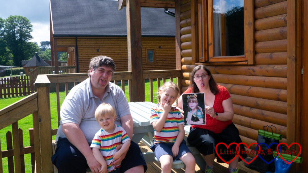 Hubby, Thomas and Sophie (in matching rainbow striped tops) and me (holding a photo of Jessica) outside our lodge at Coombe Mill pulling silly faces