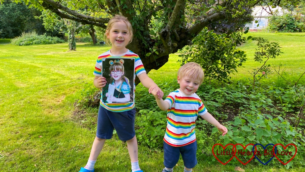 Sophie and Thomas wearing matching rainbow T-shirts and blue shorts standing in Grandma and Grandad's garden with Sophie holding a photo of Jessica