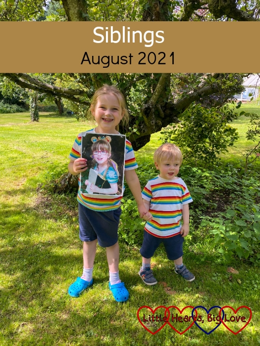 """Sophie and Thomas wearing matching rainbow T-shirts and blue shorts standing in Grandma and Grandad's garden with Sophie holding a photo of Jessica - """"Siblings - August 2021"""""""
