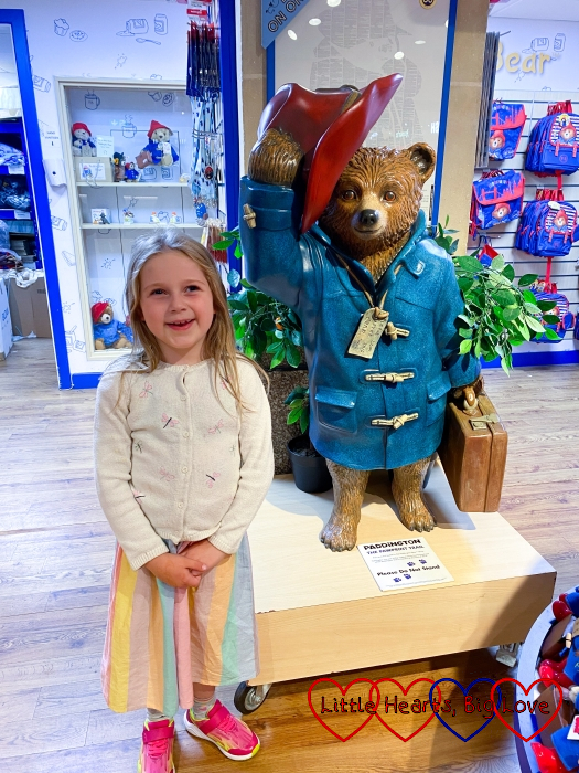 Sophie standing next to the statue of Paddington Bear at Paddington station