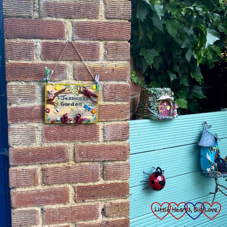 A sign saying 'Jessica's garden' next to two fairy houses and a ladybird garden ornament