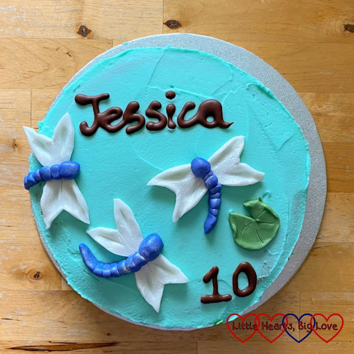 """Jessica's birthday cake - a round cake iced with aqua buttercream with three fondant dragonflies, a green fondant lilypad and the words """"Jessica"""" and """"10"""" in chocolate writing"""