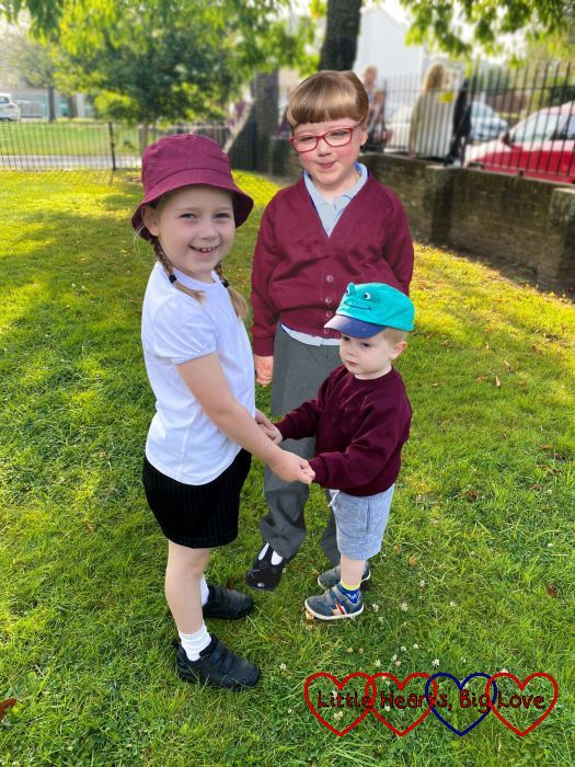 Sophie and Thomas holding hands outside school with Jessica photoshopped to be standing behind them