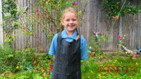 Sophie standing in her school uniform in the garden