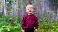 Thomas in the garden wearing his preschool jumper