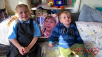 Sophie and Thomas sitting on the sofa with Jessica's photo blanket in between them